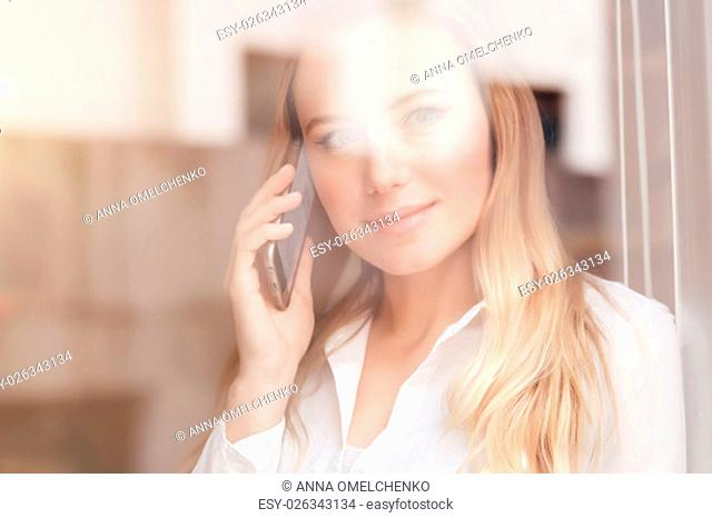 Portrait of cute blond woman standing near window at the office and talking on the phone, mobile connection, lifestyle of modern people