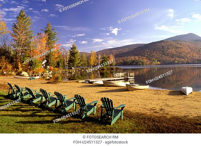 Adirondack chairs, lake, Adirondacks, New York, Blue Mountain Lake, NY, Adirondack chairs lined up along a quiet beach on the calm waters of Blue Mountain Lake...