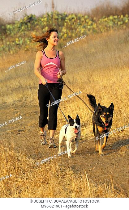 Woman with mixed breed dogs on trail, Thousand Oaks, California, USA
