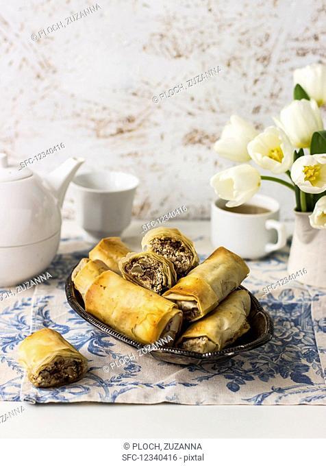 Filo rolls with Manouri cheese, walnuts, raisins, and mint; tea, white tulips