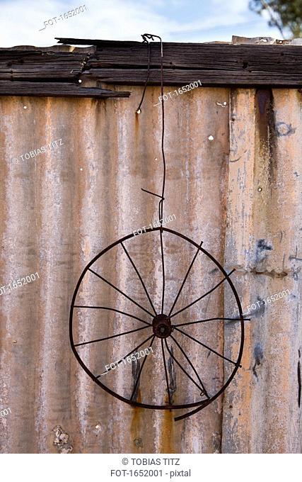 Rusty metal wheel hanging on fence