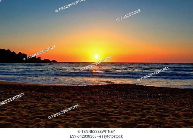 Beautiful sunset on a secluded Mediterranean sandy beach in Ghajn Tuffieha (Riviera Bay), Malta