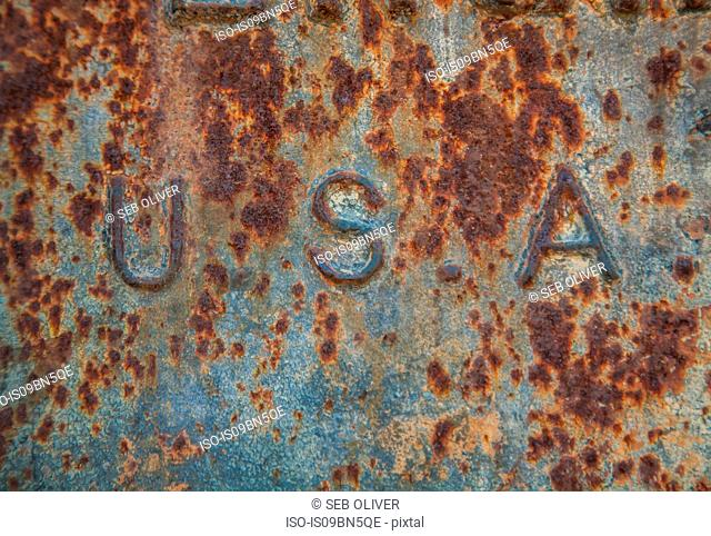 The side of a rusty iron container showing the letters USA