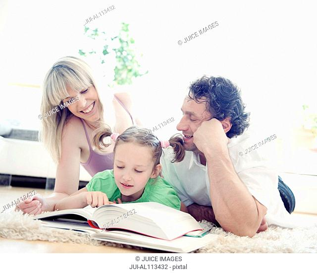 Family reading book on rug