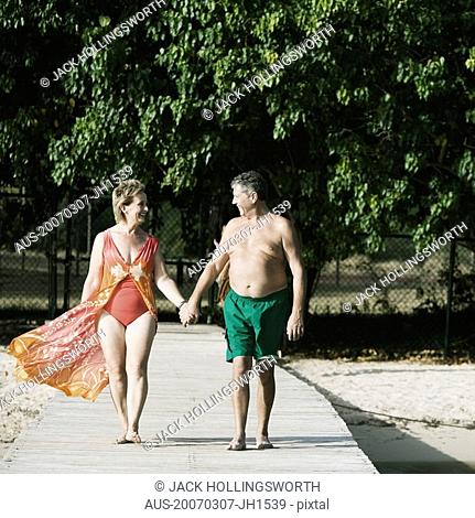 Senior man and a mature woman holding each other's hands and walking on a jetty