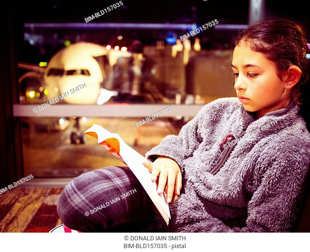 Mixed race girl reading book in airport