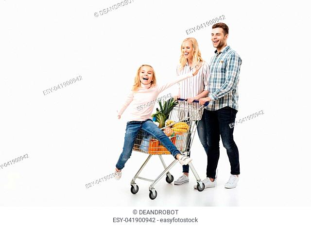 Full length portrait of a happy family walking with a shopping trolley full of groceries isolated over white background, little girl sitting in cart