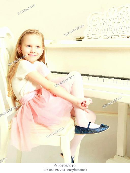 Caucasian little girl with long blond hair, in a beautiful pink skirt and white T-shirt and a pink bow on her chest.She plays music with the piano