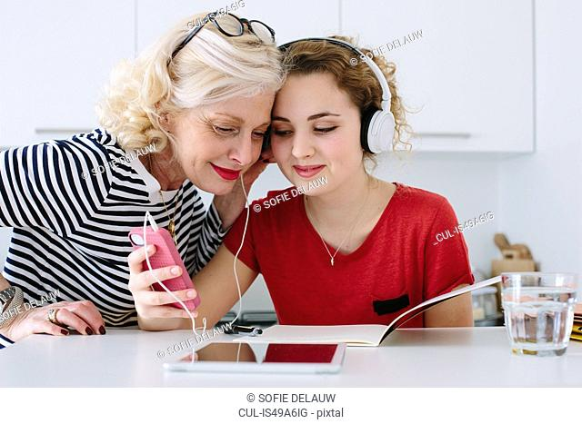 Mother and teenage daughter listening to music on headphones at home