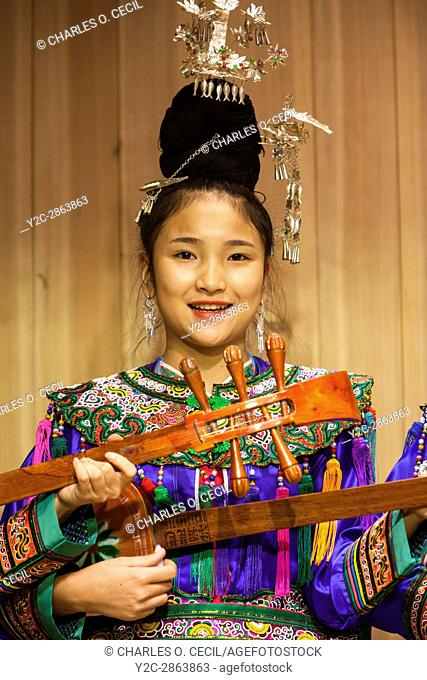 Zhaoxing, Guizhou, China. Young Woman of the Dong Ethnic Minority Playing a Pipa, a Five-stringed Lute