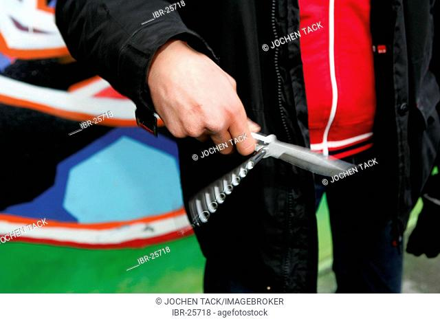 DEU, Germany : juvenile crime. Young man is playing with his flick knife.(posed scene)