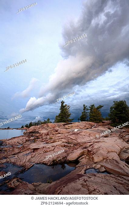 Incredible cloud formations hanging over Pink Granite along the shores of Georgian Bay in Killarney Provincial Park, Ontario, Canada