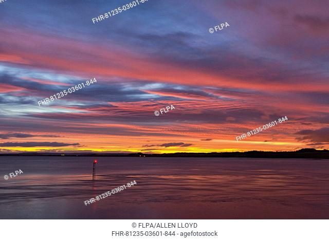 View over river estuary at dawn, with navigation light in foreground, viewed from Beachley looking towards Monmouthshire, River Severn, Severn Estuary
