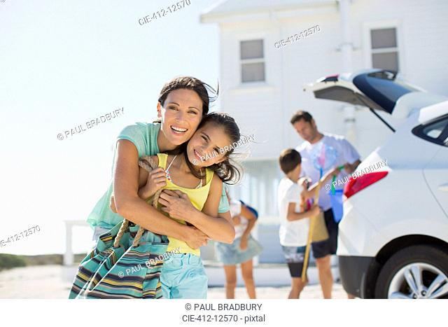 Mother and daughter hugging outside beach house