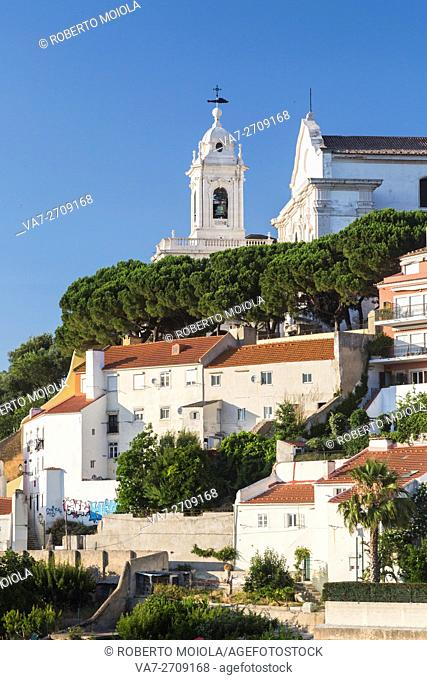 View of a residential district of Lisbon surrounded by trees and church under a blue summer sky Portugal Europe
