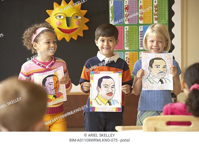 Multi-ethnic students holding up pictures in class