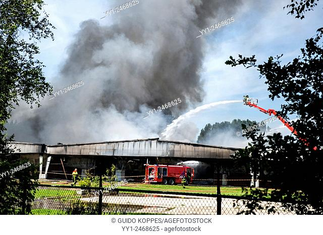 Tilburg, Netherlands. A large fire blazing inside a warehouse for plastic garden furniture at an industrial estate, with smoke nuisance as a result