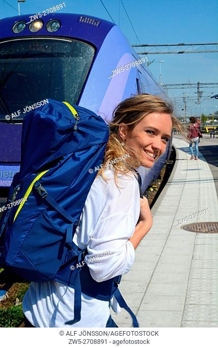 Young woman walks along a train on a railway platform in Ystad, Scania, Sweden