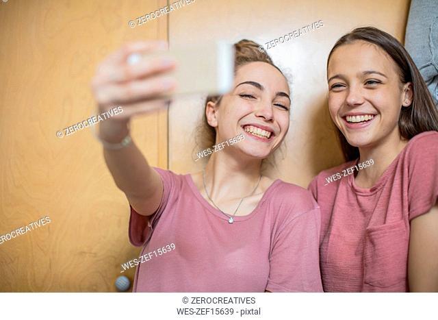 Portrait of two happy teenage girls taking a selfie