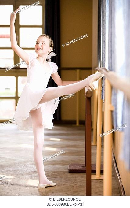 portrait of young girl exercising on ballet barre