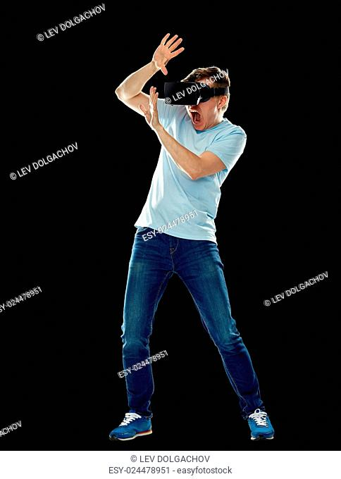 3d technology, virtual reality, entertainment and people concept - scared young man with virtual reality headset or 3d glasses playing game