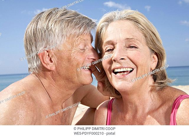 Spain, Mallorca, Happy senior couple sitting at beach