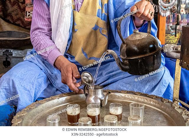 Berber man wearing turban and deraa pours tea from teapot into glasses for traditional Moroccan tea ceremony, Tighmert Oasis, Morocco