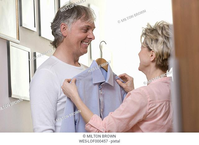Mature woman helping her husband to choose clothes for invitation