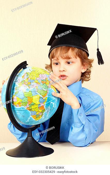Little professor in academic hat looks at a globe