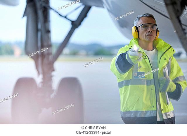 Air traffic controller with flashlight under airplane on airport tarmac