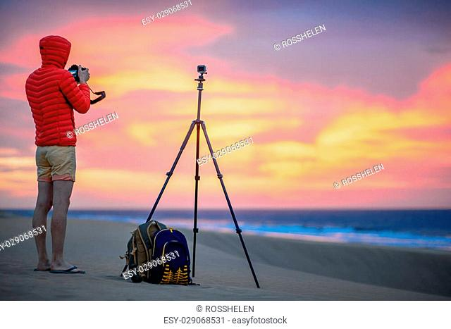 Photographer in red jacket with hood photographing and filming with small camera on the tripod sunrise on the sand dune. Time lapse filming process
