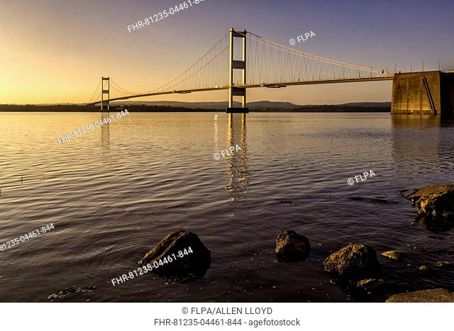View of road bridge over river at sunset, viewed from Aust, Severn Bridge (First Severn Crossing), River Severn, Severn Estuary, Gloucestershire, England