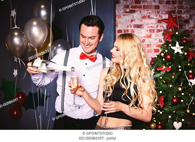 Man and woman at party, man pouring champagne into woman's glass
