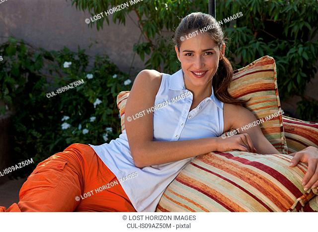 Woman relaxing on cushions, Marrakesh, Morocco