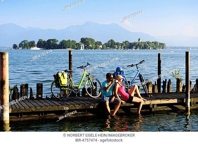 Cyclists resting on jetty, Gstadt am Chiemsee, behind Frauenchiemsee Island, Chiemgau, Upper Bavaria, Bavaria, Germany