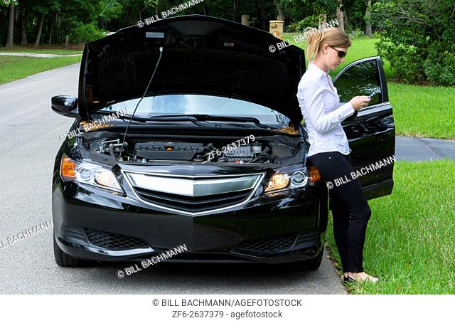 Young woman with car broken down on side of road using cell phone to call for help and being rather annoyed MR Model released