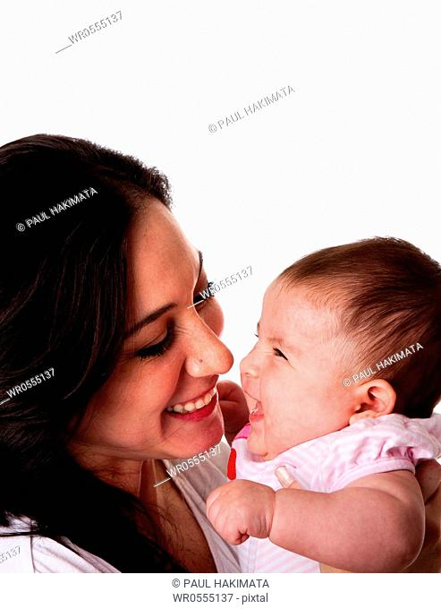 Faces of beautiful family couple of mother and daughter baby girl looking at eachother having fun and laughing, isolated