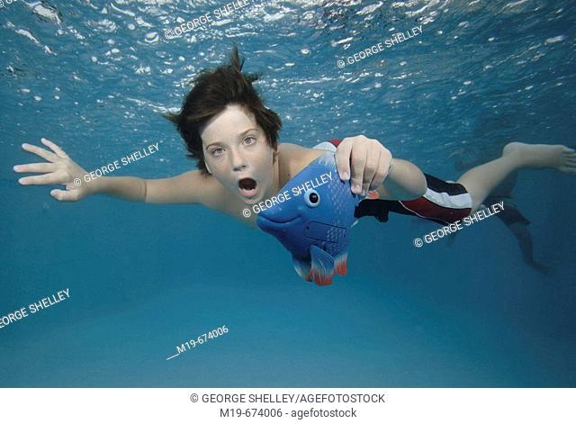 Boy swiming unnderwater with a fish