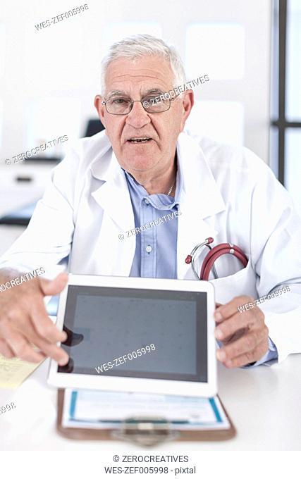 Serious senior doctor at desk showing digital tablet
