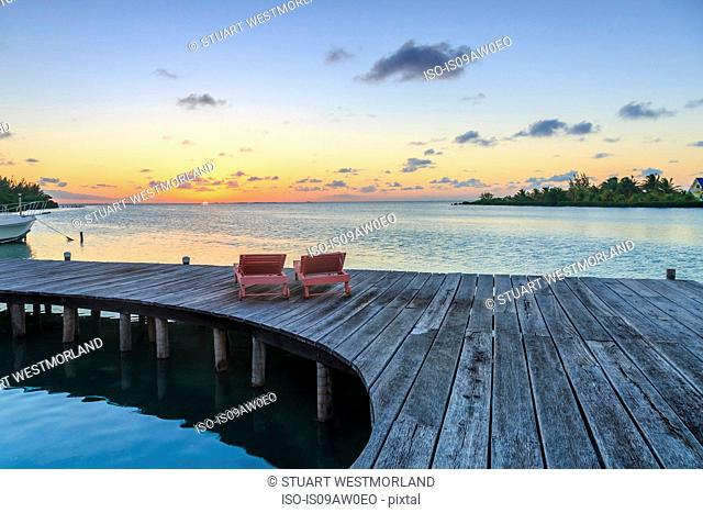 Two sun loungers on waterfront boardwalk at sunset, St. Georges Caye, Belize, Central America