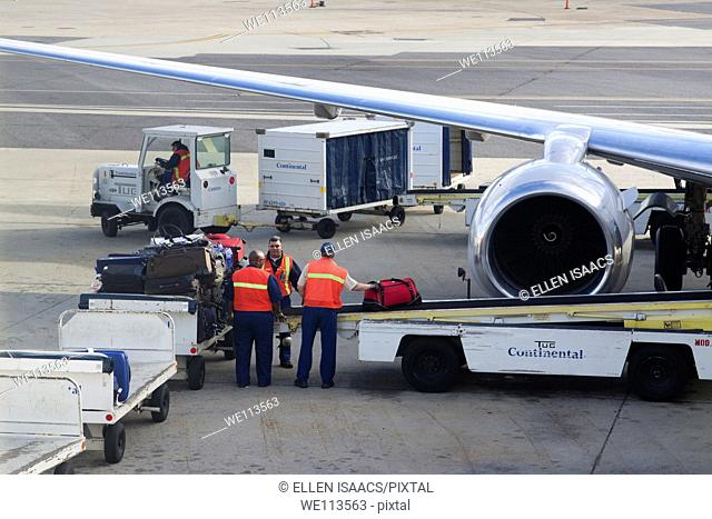 Baggage handlers loading luggage onto a convey into an airplane on the tarmac of New Orleans Airport