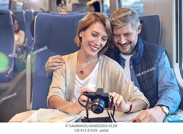 Smiling, affectionate couple looking at photographs on digital camera on passenger train