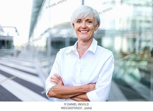 Portrait of smiling senior businesswoman outside
