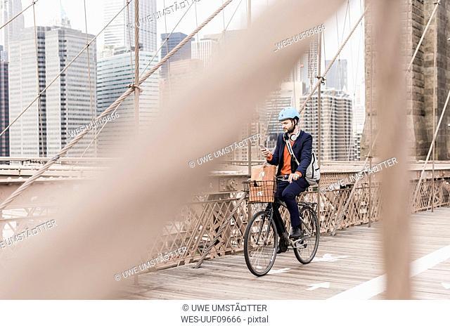USA, New York City, man on bicycle on Brooklyn Bridge using cell phone
