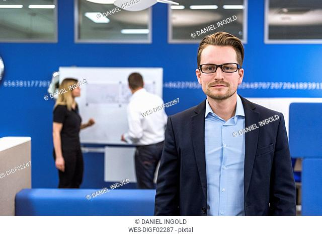 Businessman standing in conference room, while colleagues working with flipchart in background