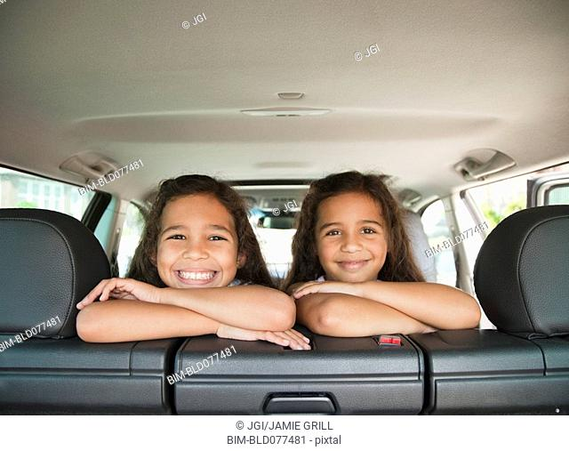 Hispanic sisters in back seat of car