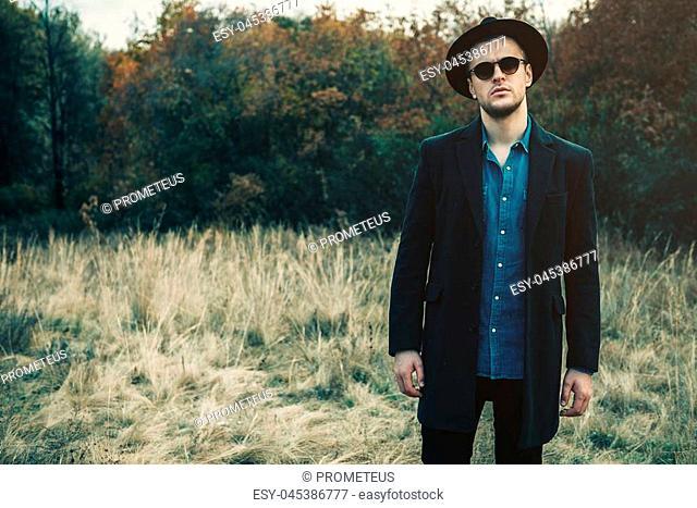 Seasonal autumn fashion. Portrait of a handsome man wearing black coat, a hat and sunglasses. Autumn nature