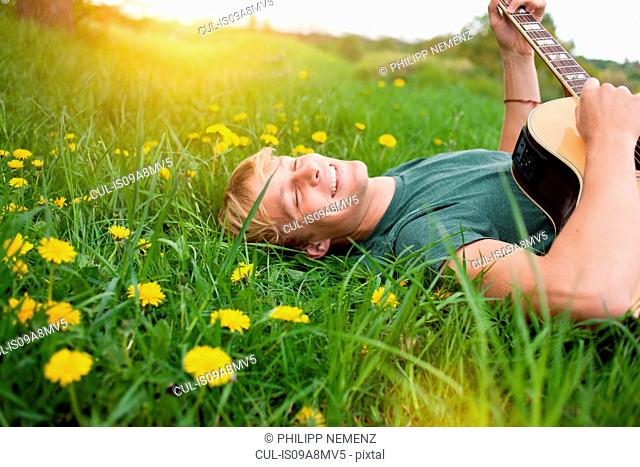 Young man lying in grass playing guitar