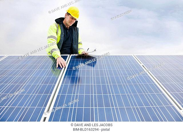 Caucasian technician examining solar panels