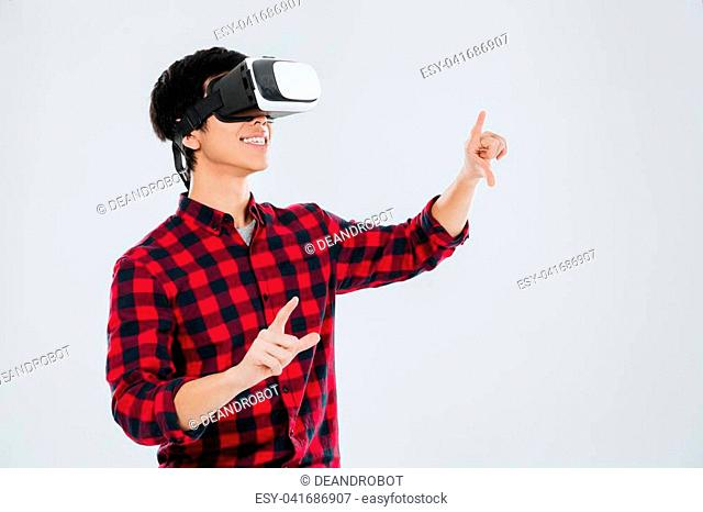 Asian man dressed in casual shirt in a cage and wearing virtual reality device and pointing. Isolated over white background